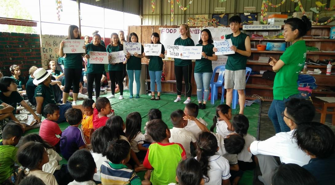 Children listen to a public health lesson on healthy living.